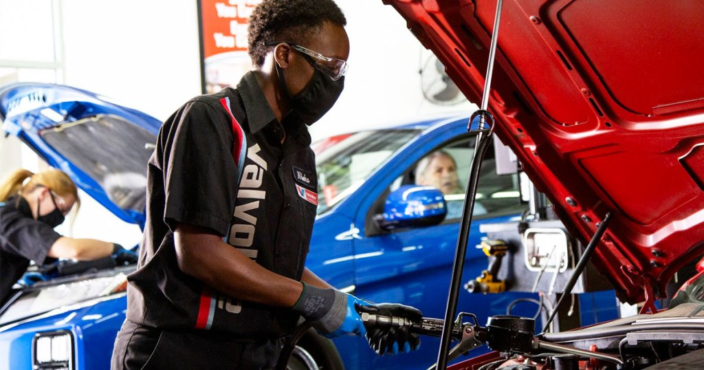 man wearing face mask adding oil into engine of a red car