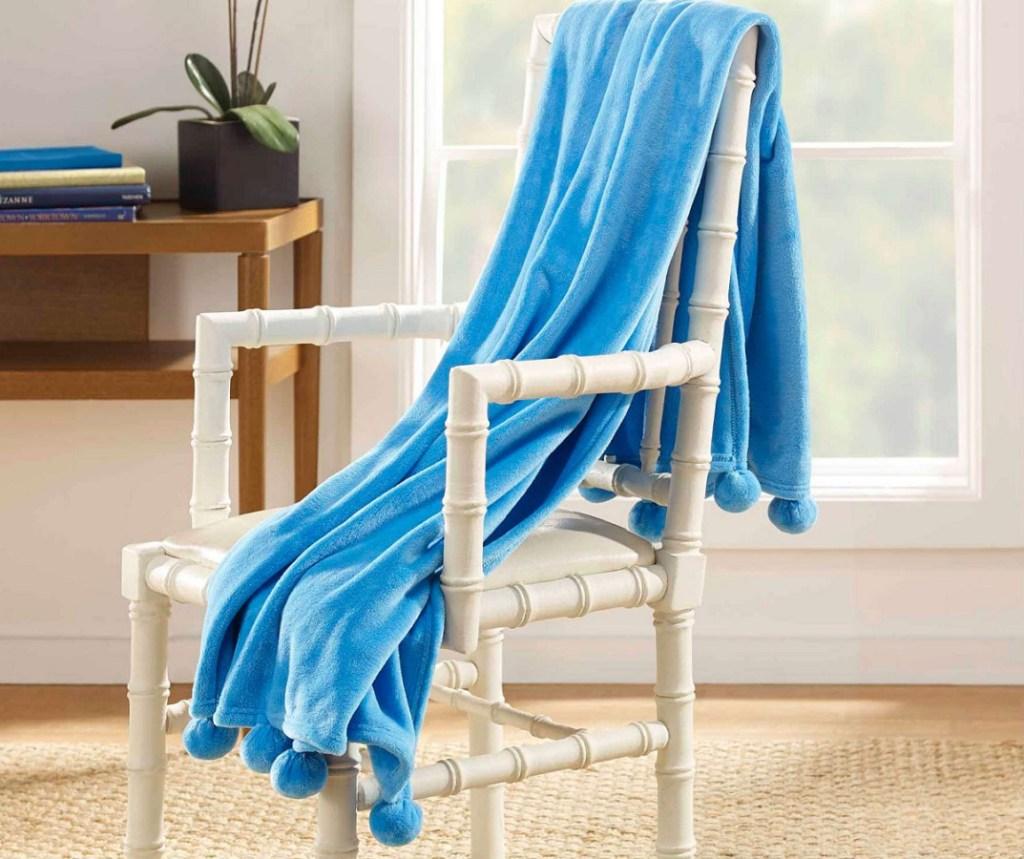 blue pom pom throw draped over white chair