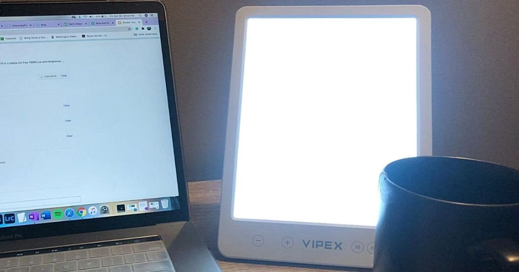 Vipex light therapy lamp next to laptop