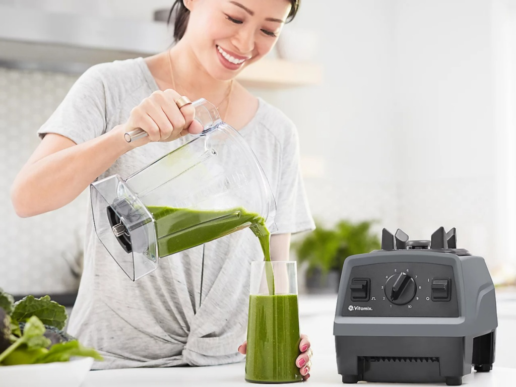 woman using a vitamix blender and pouring a green smoothie into a glass