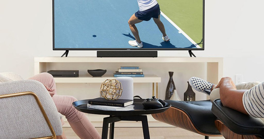 people watching tv with a black soundbar on tv stand