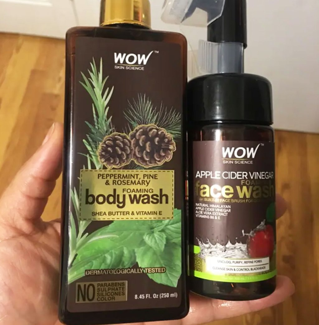 person holding up two brown bottles of wow skincare science body wash and face wash