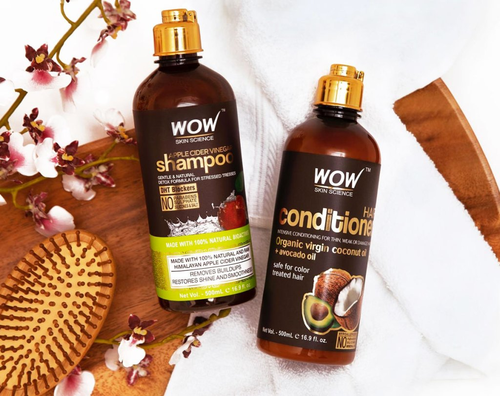 brown bottles of wow skincare science shampoo and conditioner laying on white towels near wooden hair brush
