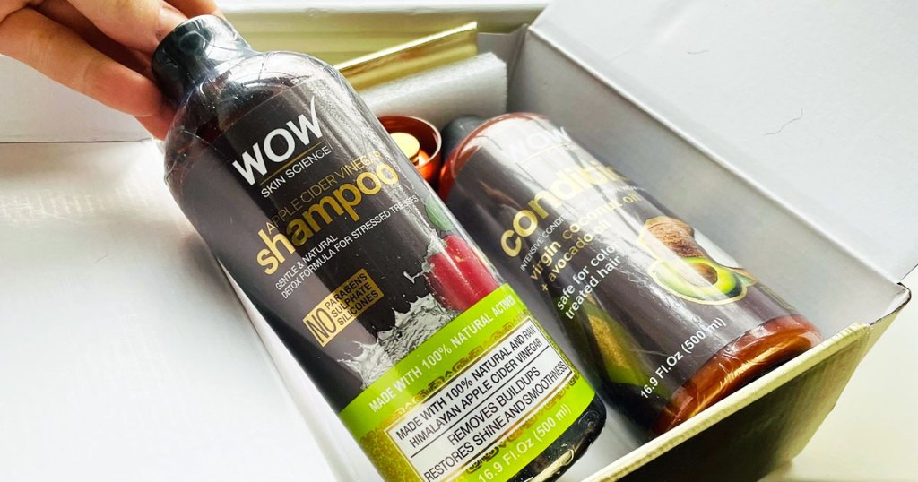 two bottles of wow shampoo and conditioner inside a box with person lifting up the bottle of shampoo