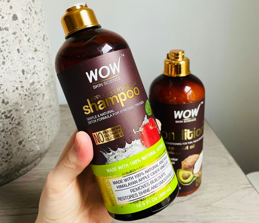 person holding up brown bottle of wow shampoo with bottle of conditioner in background