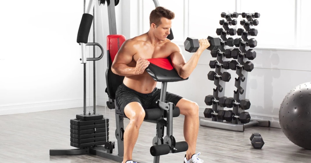 man sitting on a workout bench at home lifting weights