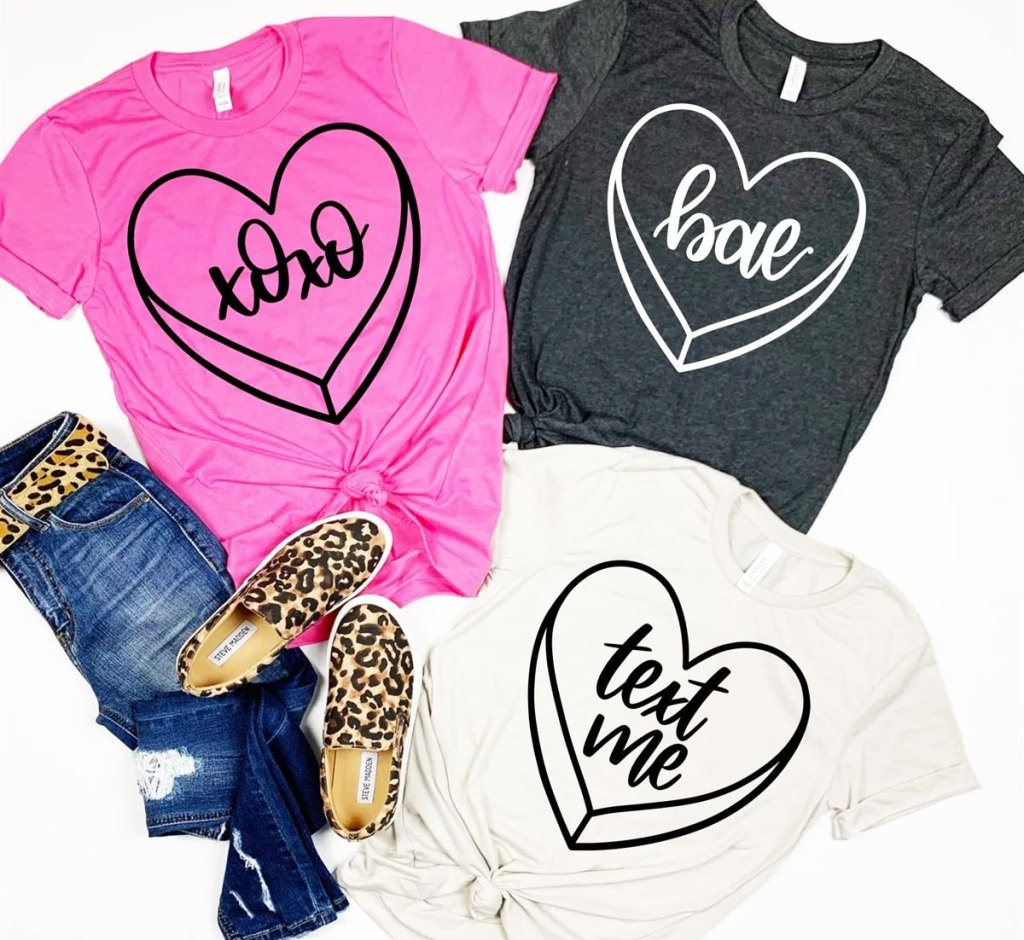 three women's tees in pink, black, and white with conversation hearts on them