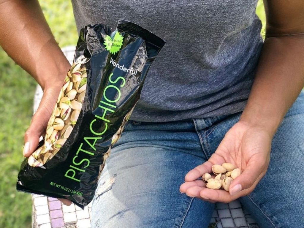woman eating pistachios sitting on grass