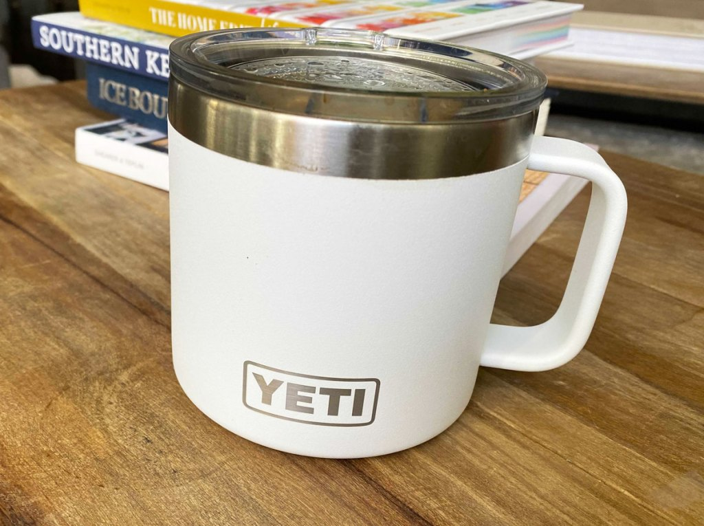white yeti rambler mug on a wood table