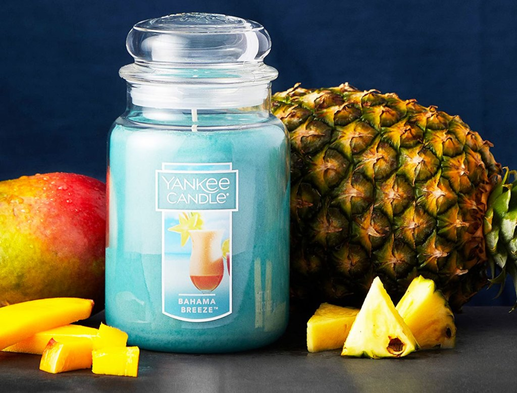 large blue yankee candle in bahama breeze scent with pineapple and mango behind it