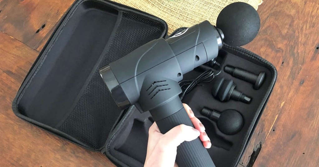 person holding up a black massage gun with case and attachments in background