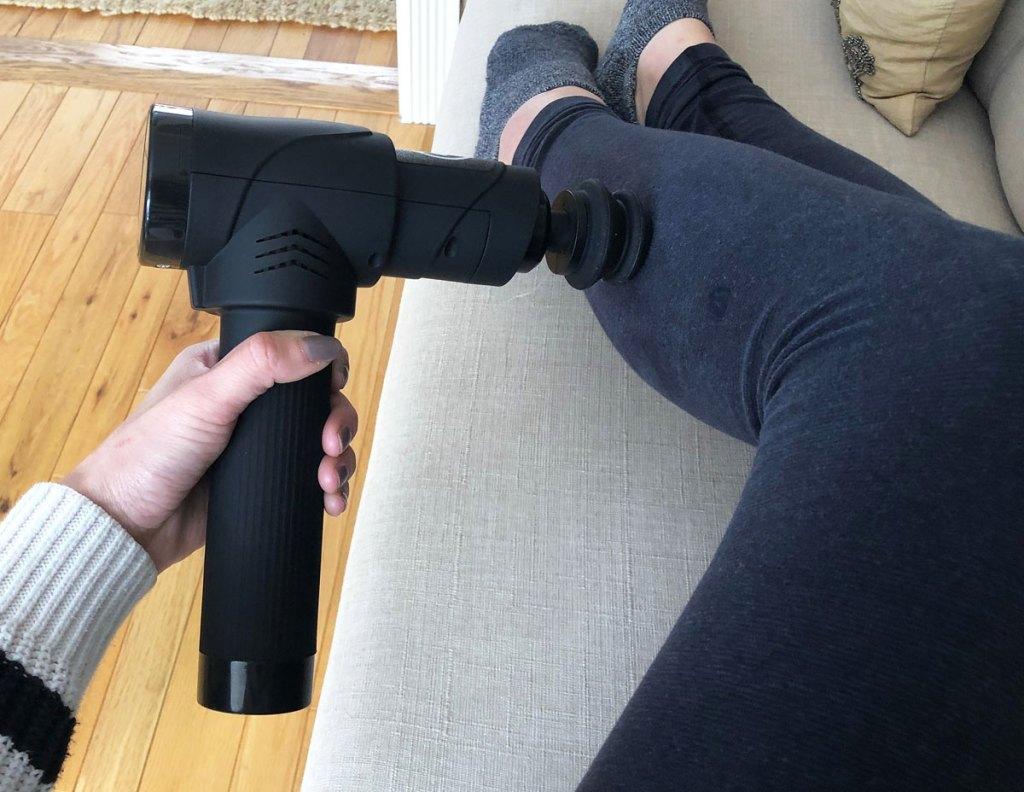 woman using black massage gun on her leg