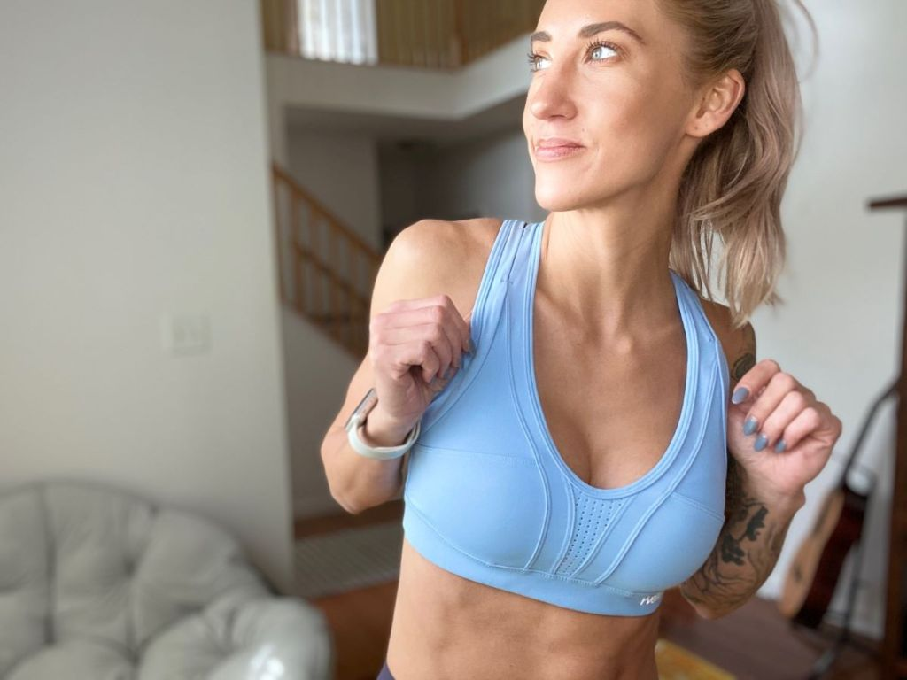 woman holding on to the straps of her sports bra