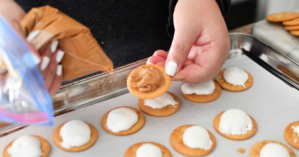 adding peanut butter to ritz cracker