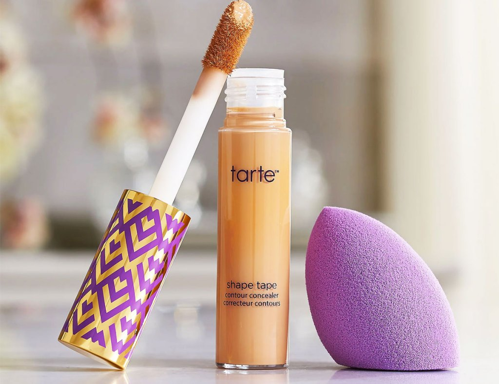 tube of tarte shape tape concealer with a purple blending sponge next to it