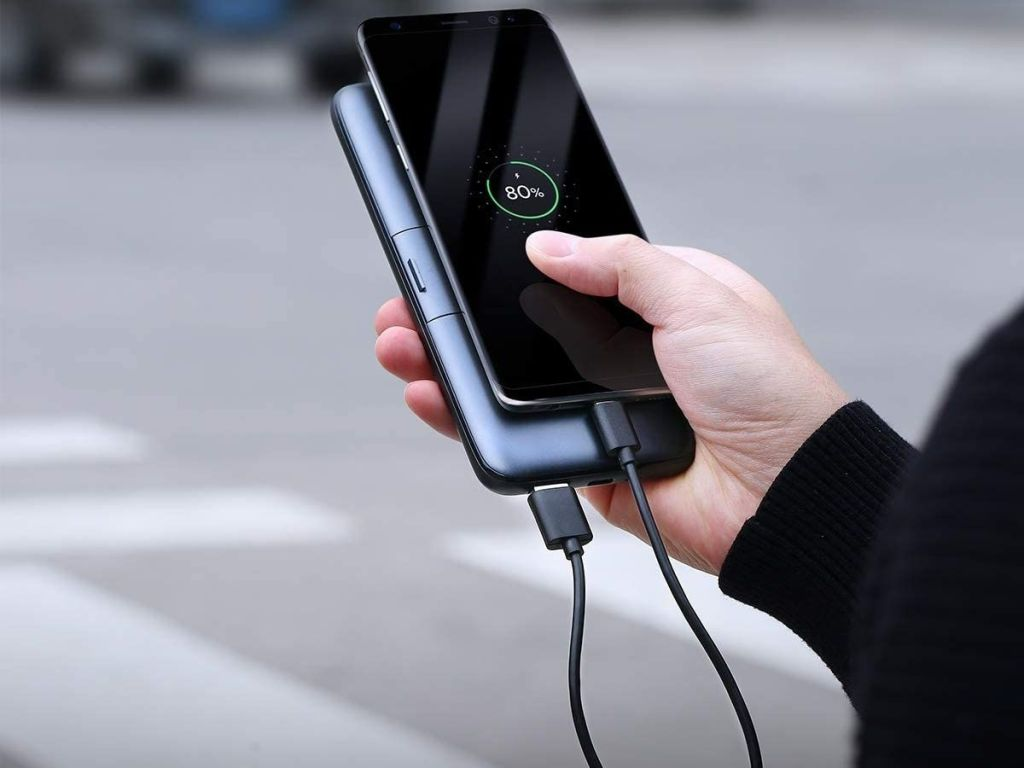 hand holding phone being charged