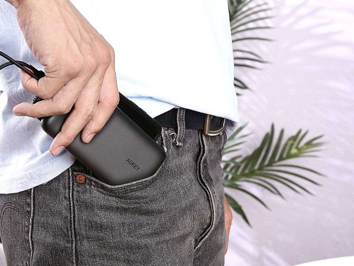 man putting black Aukey power bank in his jeans