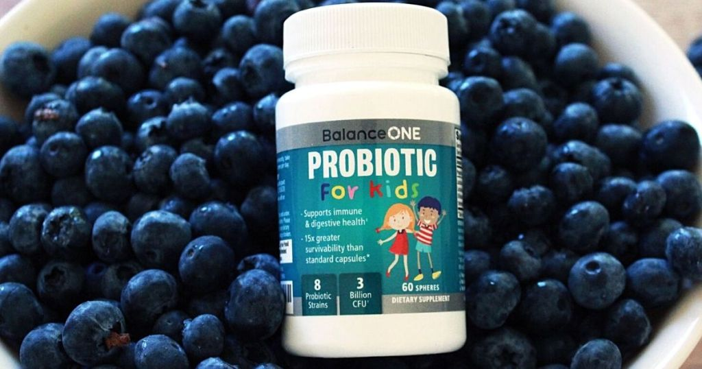 bottle of probiotics in a bowl of blueberries
