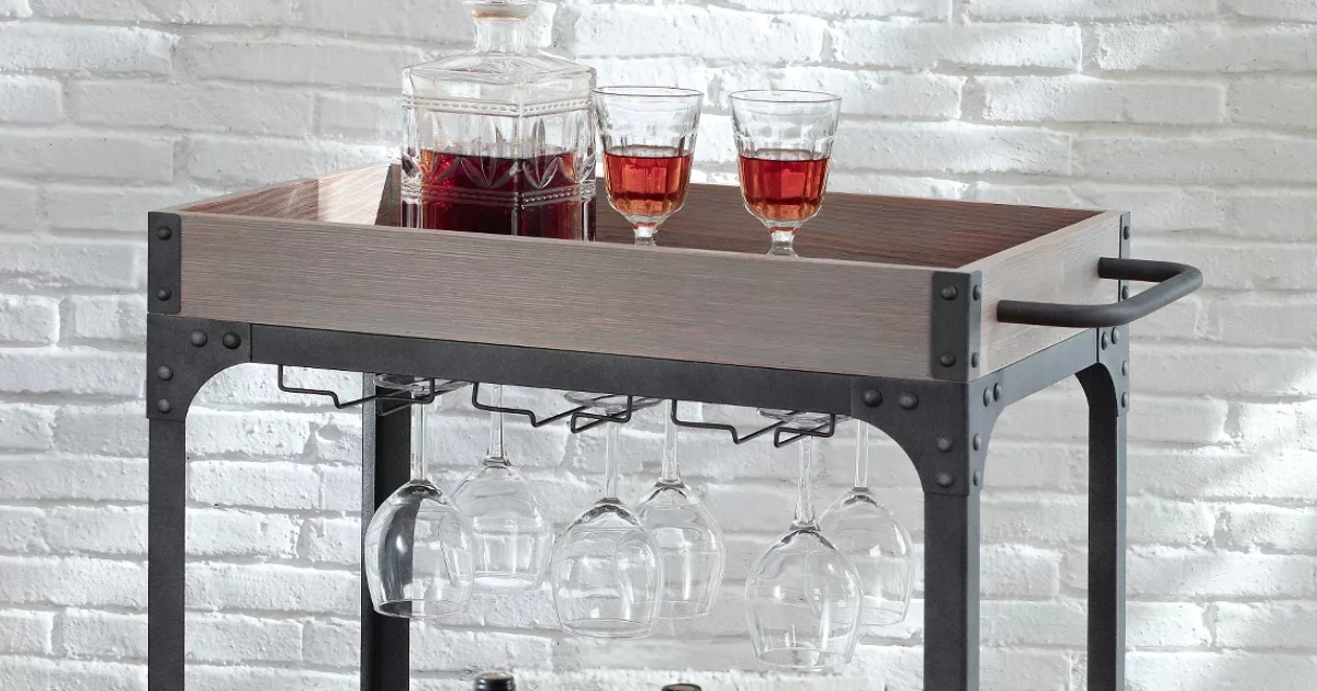 top portion of a rustic metal and wood bar cart. two filled wine glasses on top and empty wine glasses hanging below the shelf