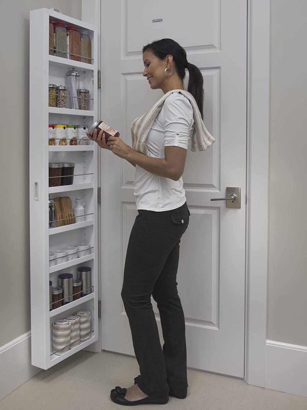 woman looking at jar of food in front of behind the door pantry organization idea