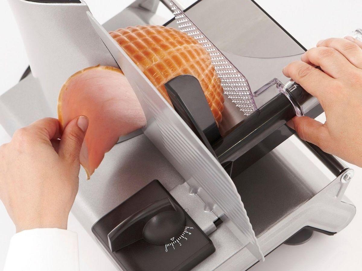 hands using meat slicer to slice ham