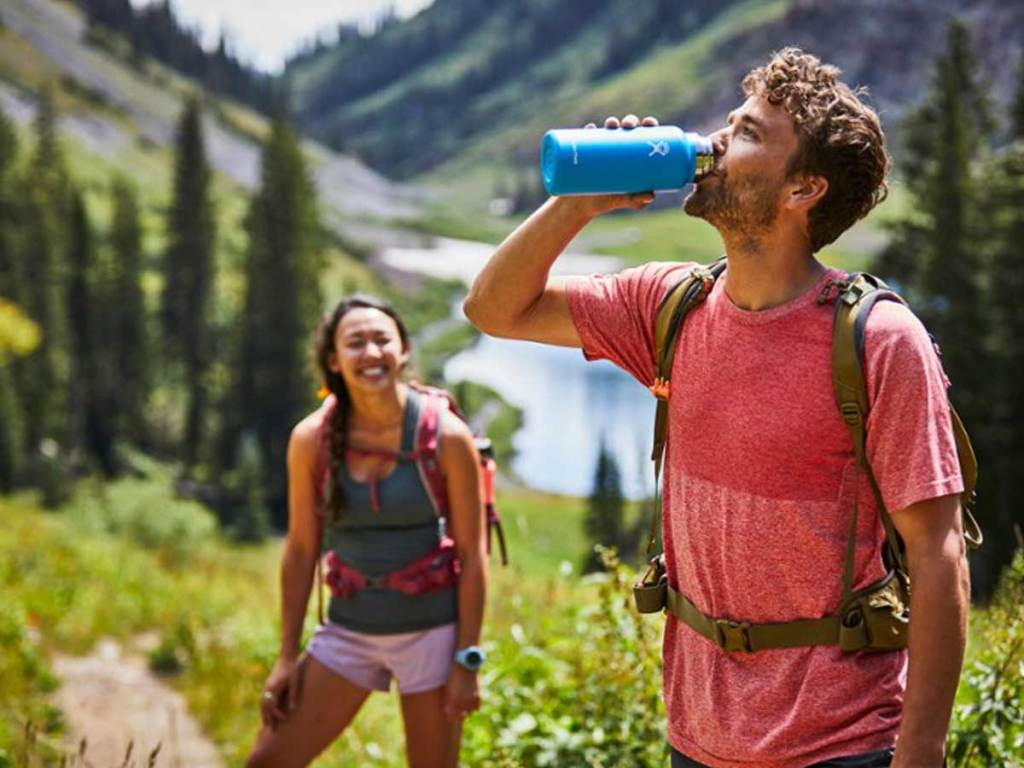 man drinking from water bottle while hiking in mountains