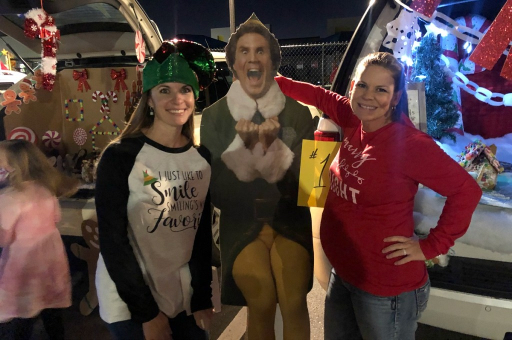 two women standing on either side of a buddy the elf cardboard cutout standee