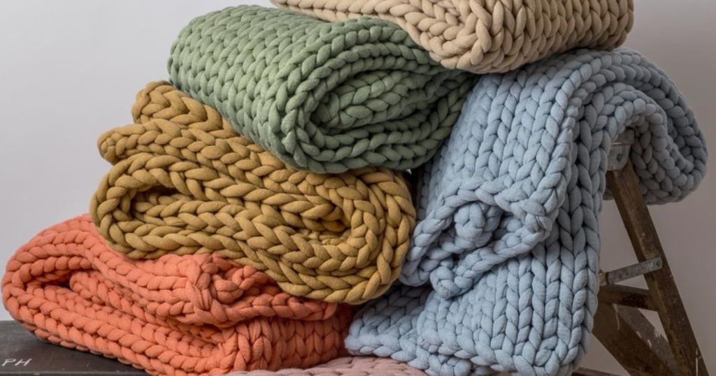 chunky knit blankets in many colors piled up
