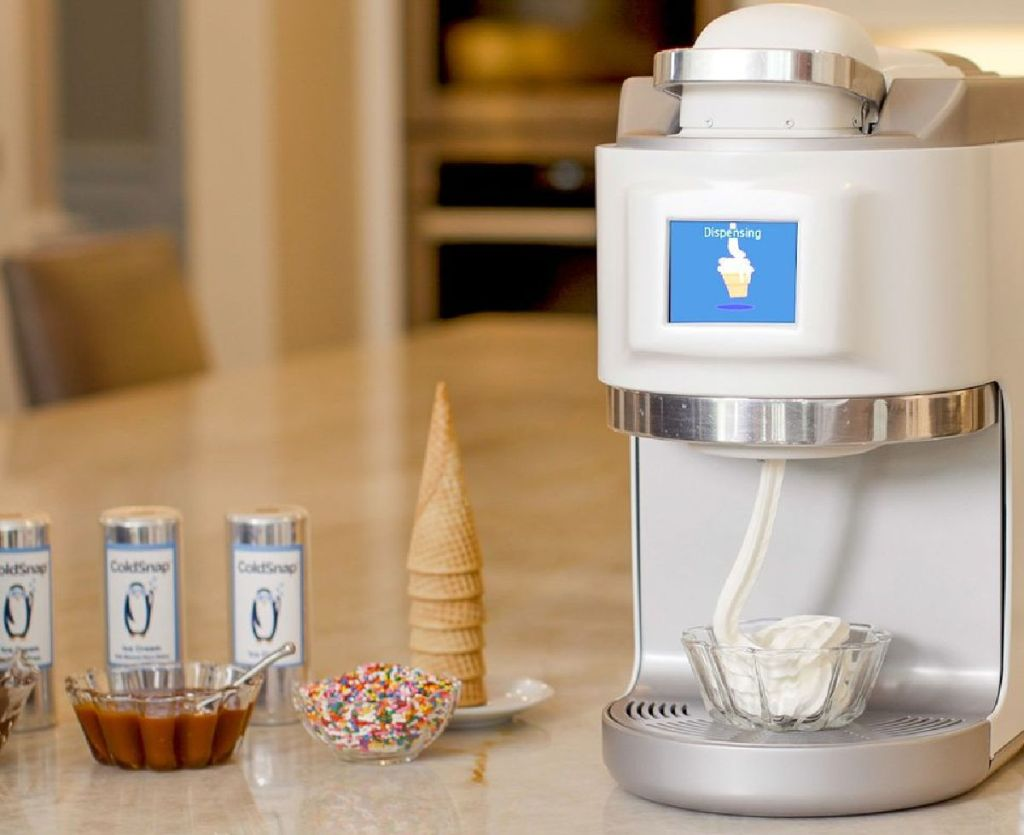 ice cream machine next to cones and toppings