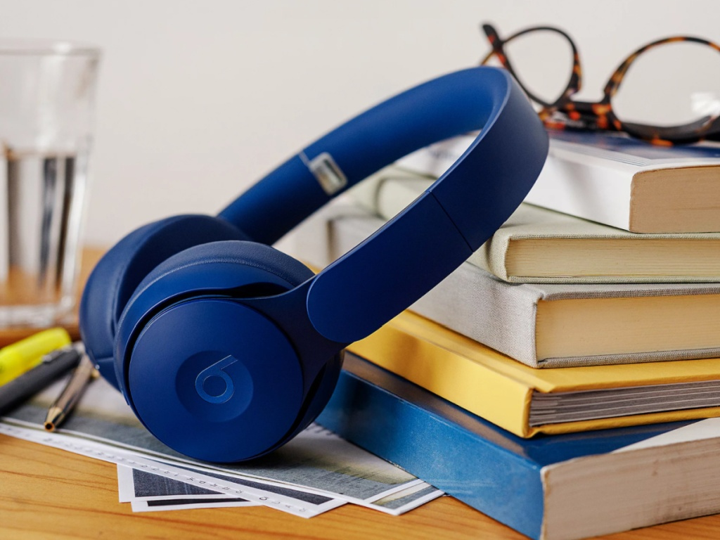 dark blue dark blue solo beats dr. dre leaning on a stack of books