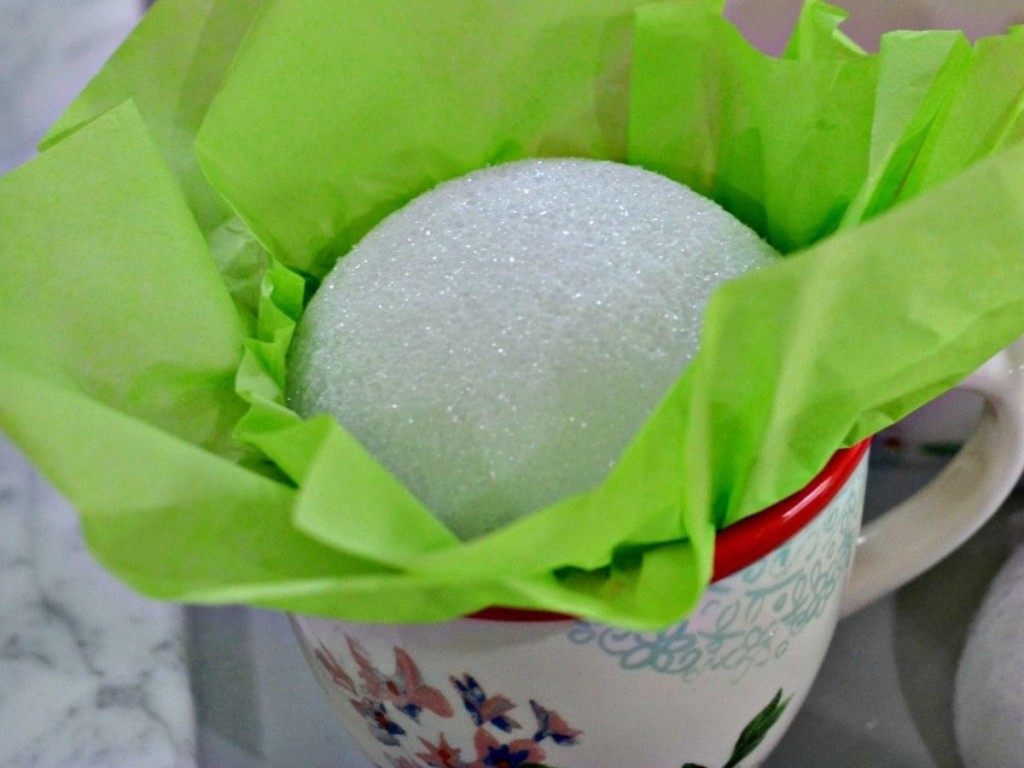 foam ball and green tissue paper in coffee mug