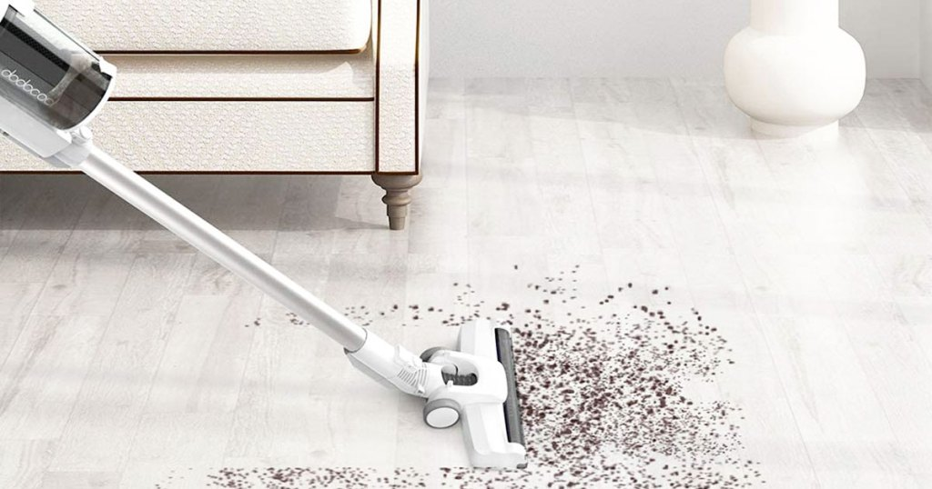 white stick vacuum cleaning up dirt on floor