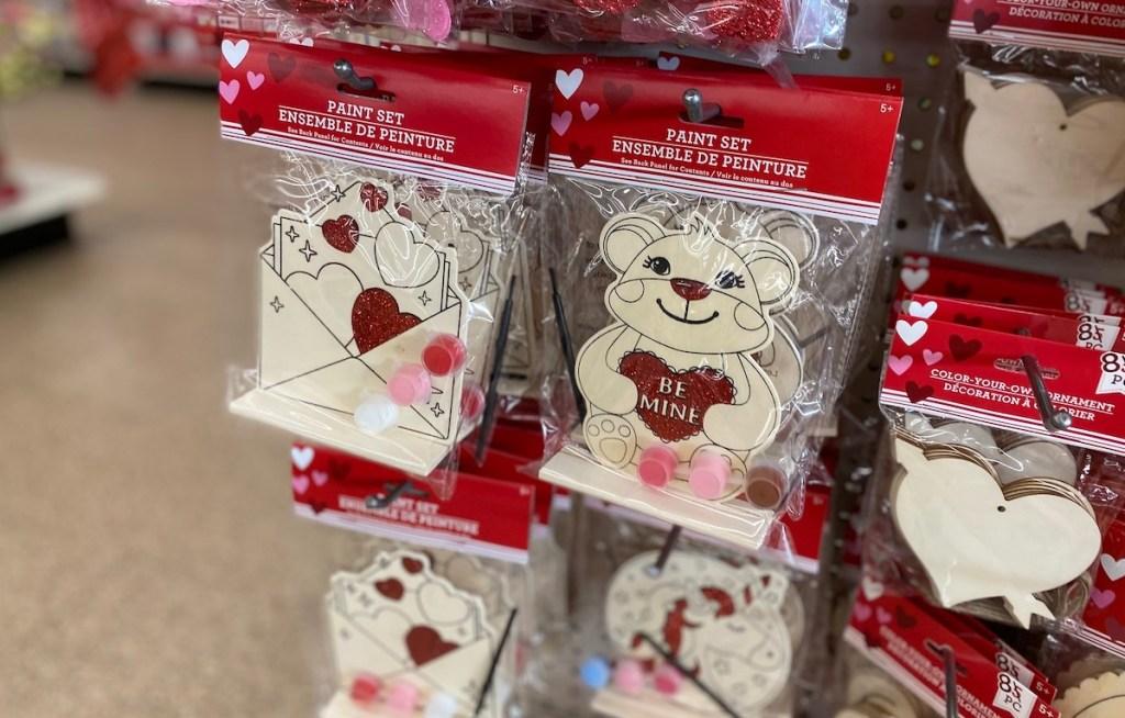 wood and glitter dollar tree valentines craft kits hanging on shelf