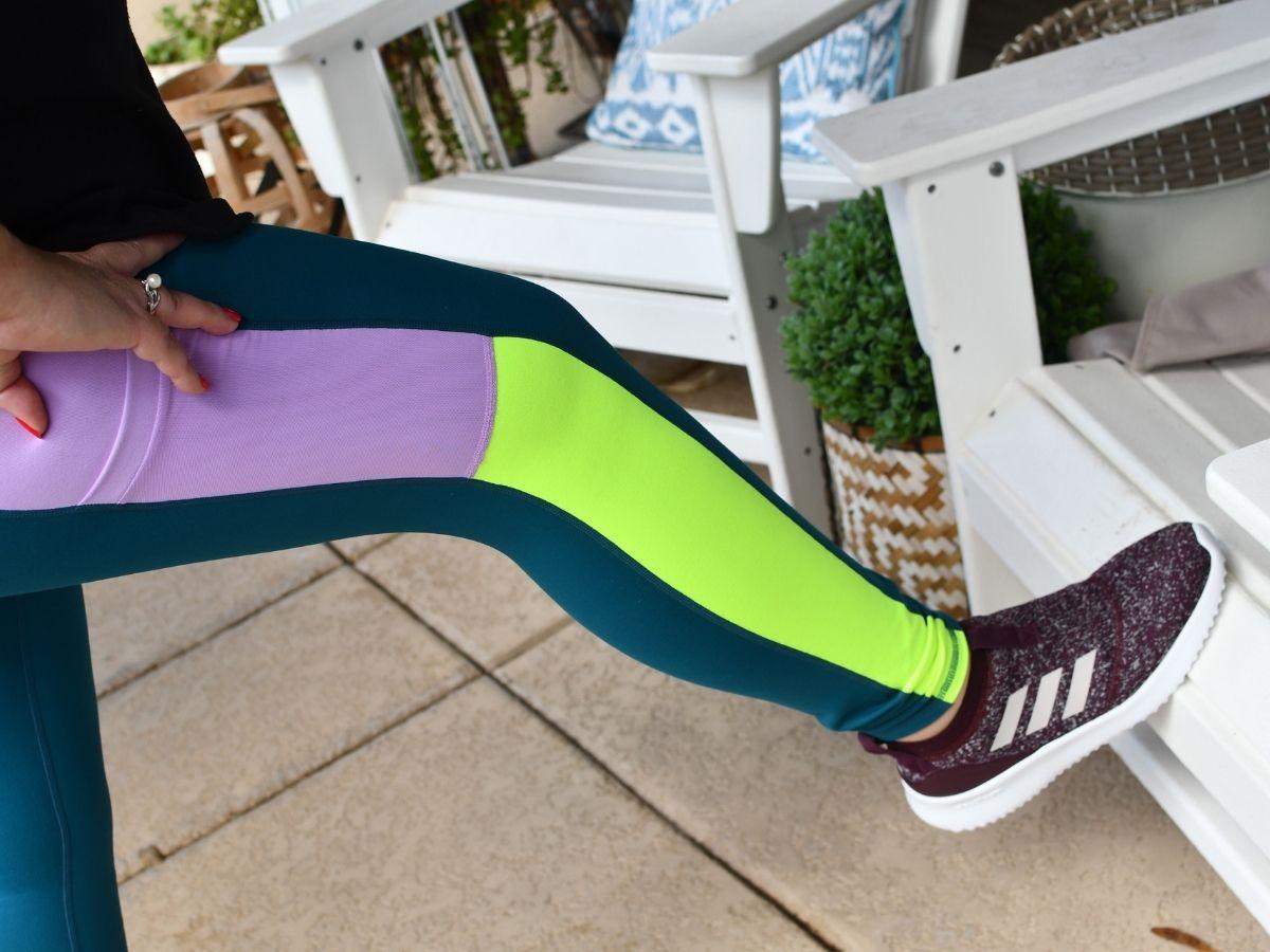 woman stretching leg wearing purple and green leggings