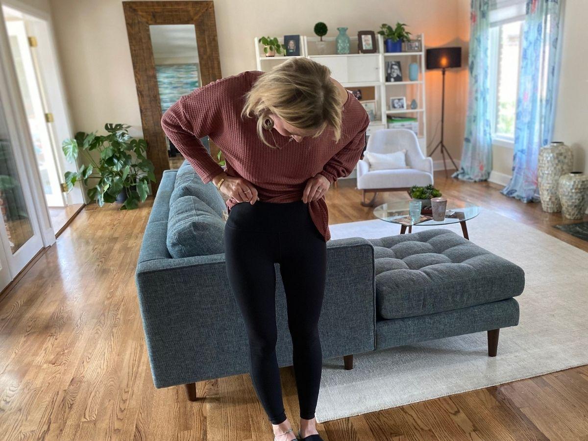 woman looking down wearing black leggings