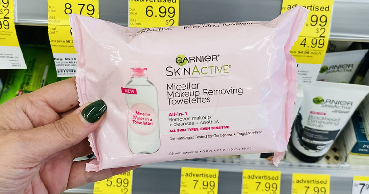 manicured hand holding pink pack of makeup wipes by store display