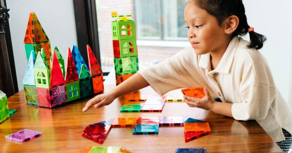girl playing with magna-tiles on table