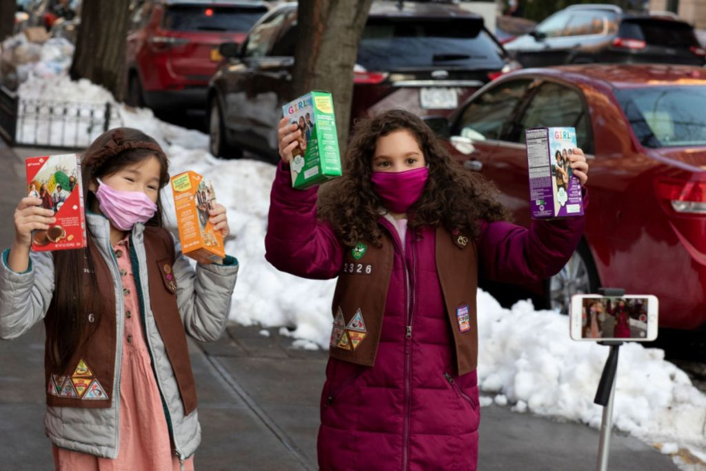 masked Girl Scouts holding boxes of cookies