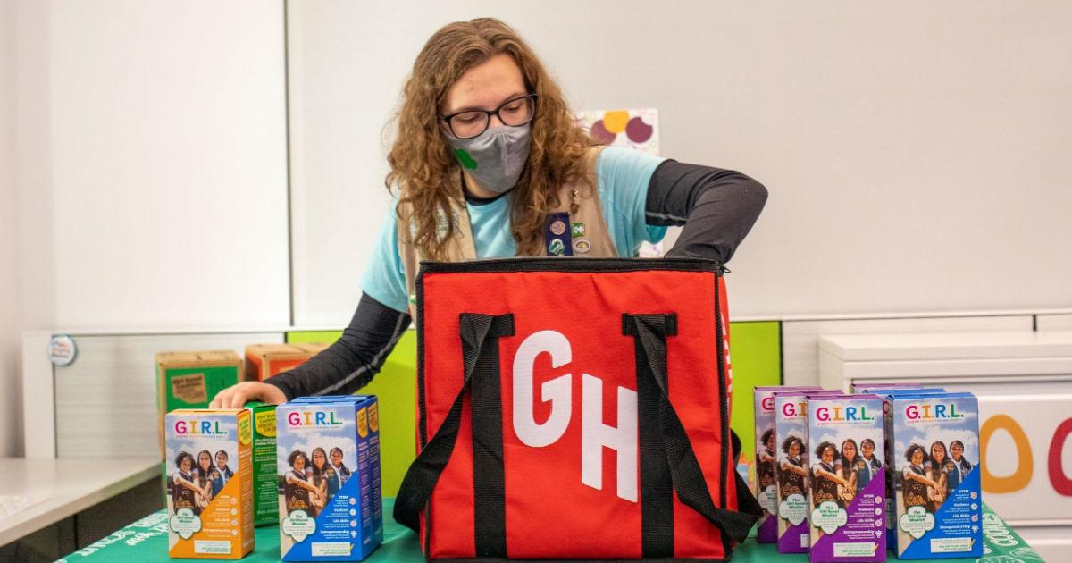 Girl Scout putting cookies in GrubHub bag