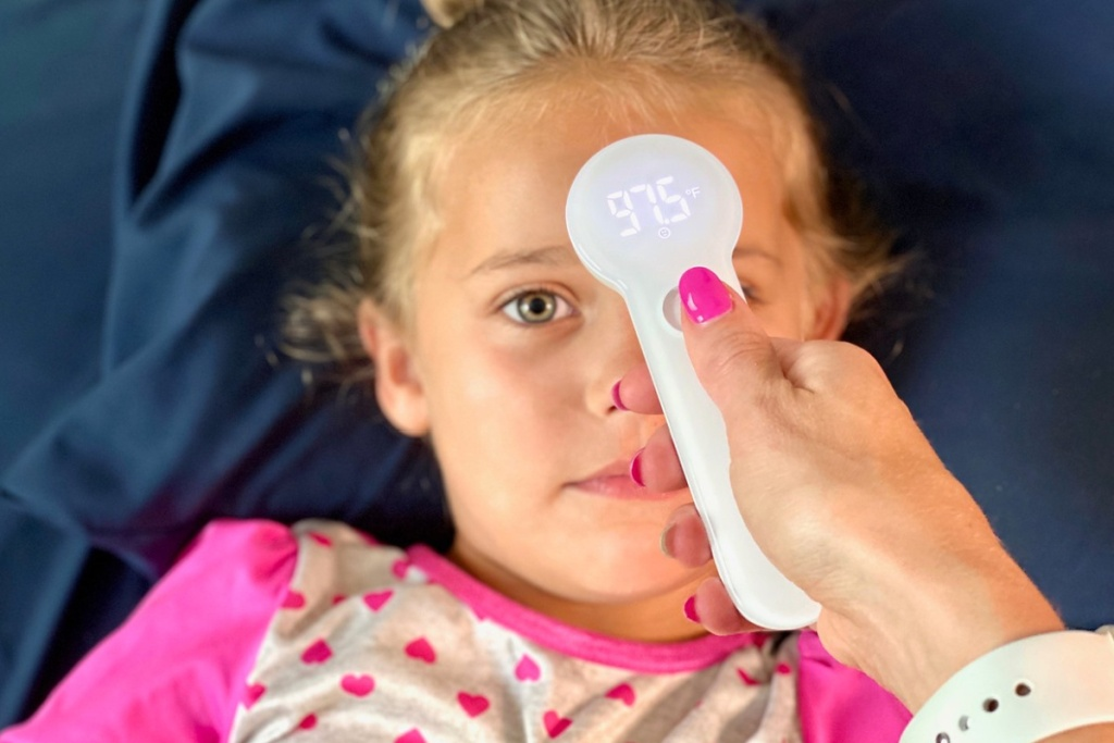 girl with thermometer to forehead