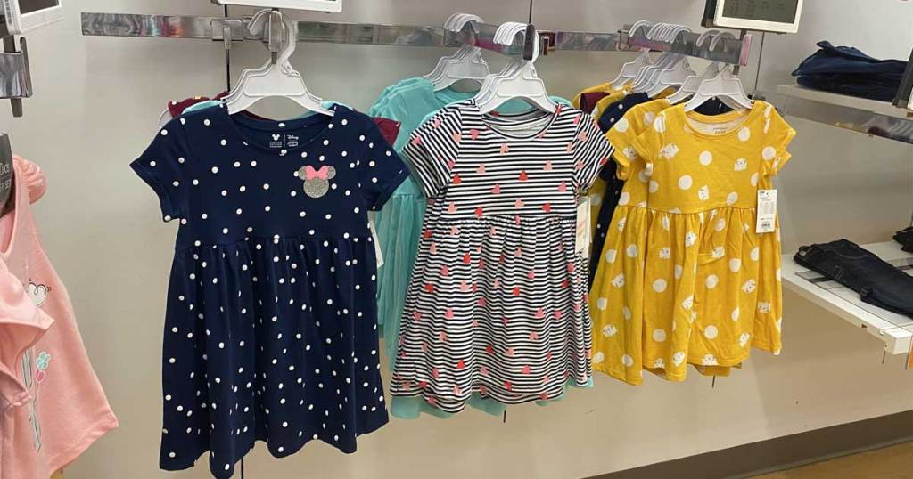 little girls dresses hanging up on display in store