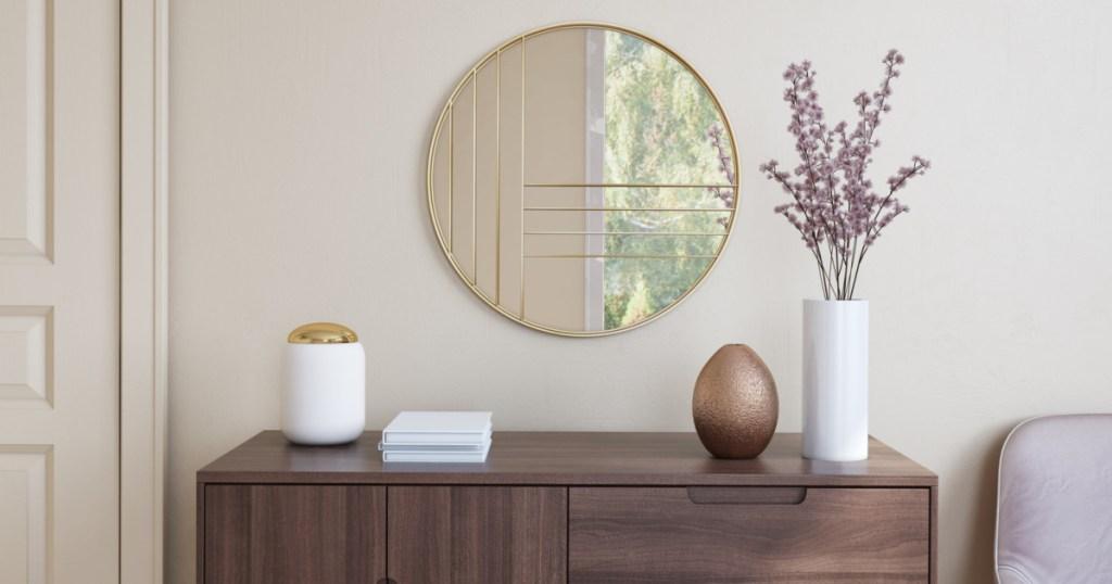 gold circle mirror above dresser