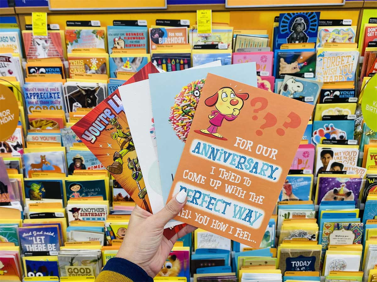 hand holding up four greeting cards in store