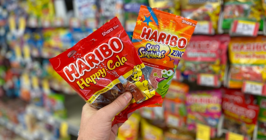 hand holding packs of haribo happy cola and sour streamers