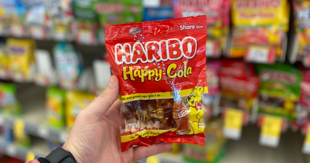 Holding a bag of happy cola gummies