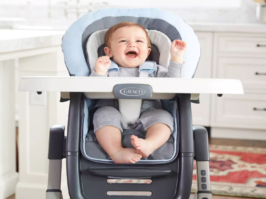 laughing baby in high chair in kitchen