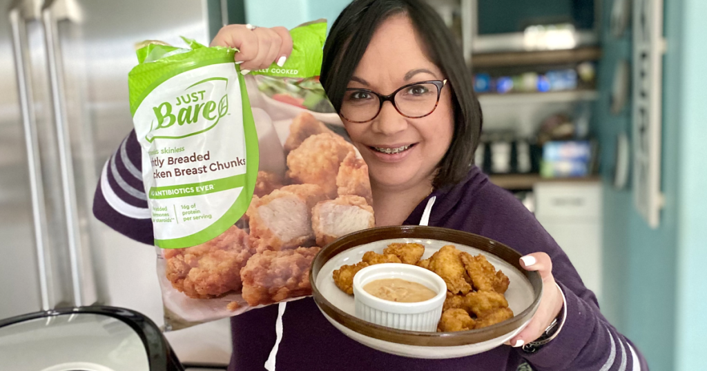 woman holding Just Bare chicken nuggets