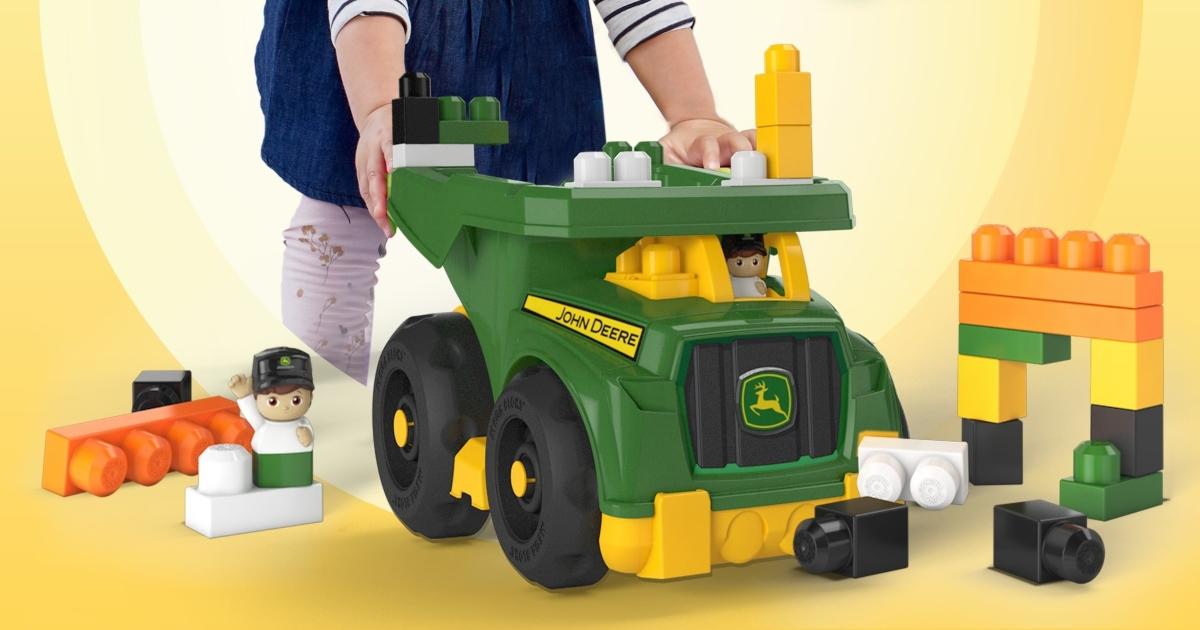 toddler on floor pushing plastic John Deer Dump Truck with large blocks