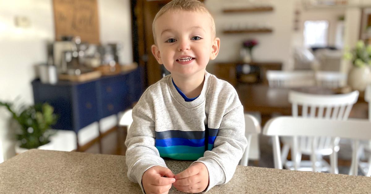 boy sitting at countertop wearing blue and green stripe sweatshirt