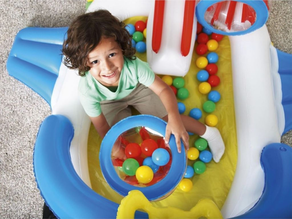 boy playing in ball pit